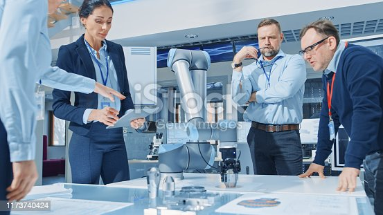 istock Diverse Team of Industrial Robotics Engineers Gathered Around Table With Robot Arm, They Manipulate and Program it to Pick Up and Move Metal Component. Bright Facility, Creative People 1173740424