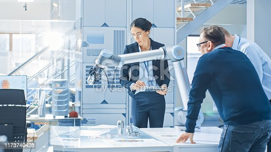 istock Diverse Team of Industrial Robotics Engineers Gathered Around Table With Robot Arm, They Manipulate and Program it to Pick Up and Move Metal Component. Bright Facility, Creative People 1173740428