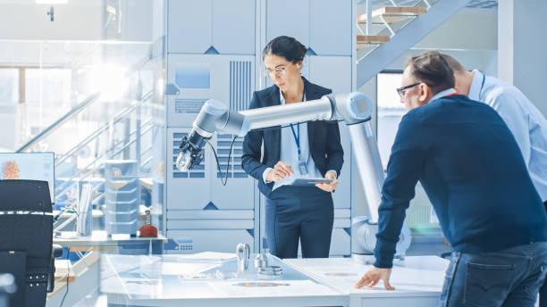 diverso equipo de ingenieros de robótica industrial reunido alrededor de la mesa con brazo de robot, que manipular y programar para recoger y mover componentes metálicos. instalaciones brillantes, personas creativas - robótica fotografías e imágenes de stock