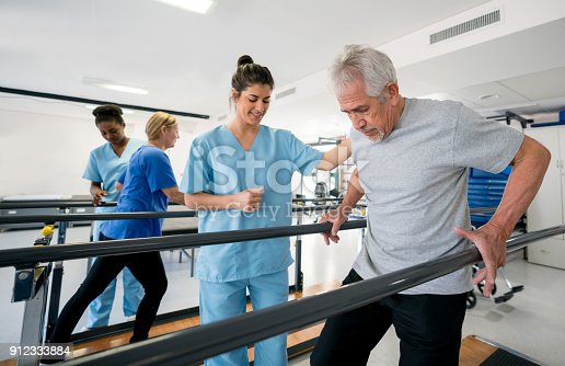 istock Diverse team of physiotherapist helping patients walk between parallel bars 912333884