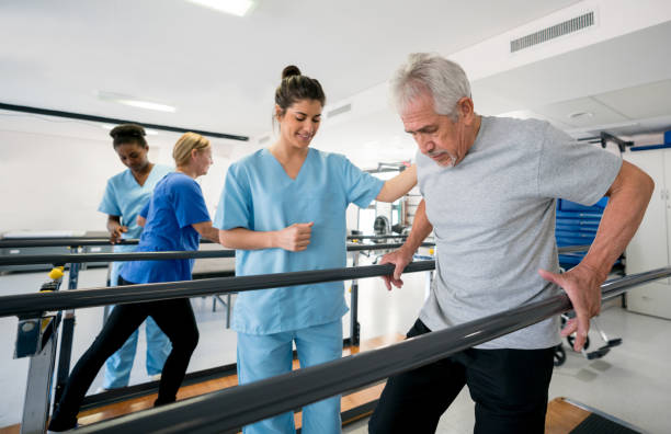 Diverse team of physiotherapist helping patients walk between parallel bars stock photo