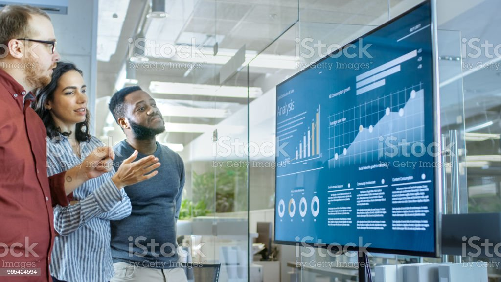 Diverse Team of Young People in Conference Room Have Discussion about Statistics and Graphs Shown on a Presentation TV. royalty-free stock photo