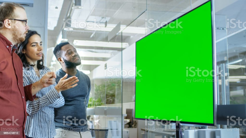 Diverse Team of Young People in Conference Room Have Discussion about Green Screen Chroma Key Template Shown on a Presentation TV. royalty-free stock photo