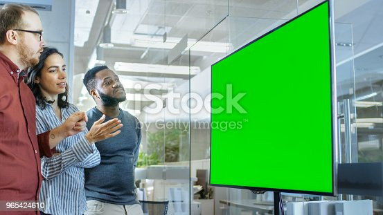 649403294 istock photo Diverse Team of Young People in Conference Room Have Discussion about Green Screen Chroma Key Template Shown on a Presentation TV. 965424610