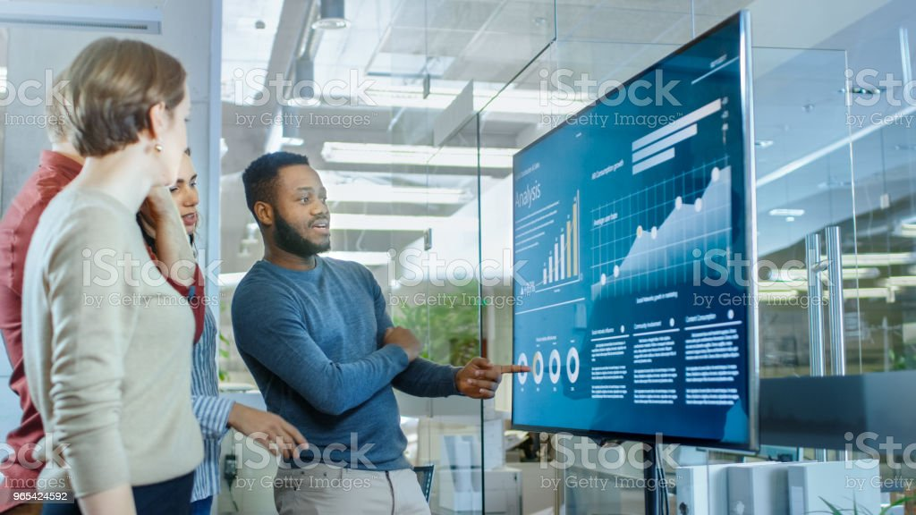 Diverse Team of Young Professionals in Conference Room Have Discussion about Statistics and Graphs Shown on a Presentation TV. royalty-free stock photo
