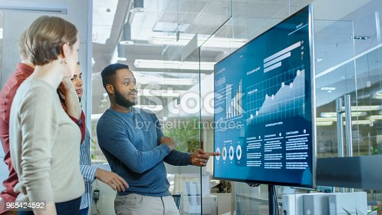 649403294 istock photo Diverse Team of Young Professionals in Conference Room Have Discussion about Statistics and Graphs Shown on a Presentation TV. 965424592