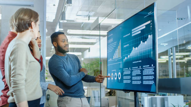 Diverse Team of Young Professionals in Conference Room Have Discussion about Statistics and Graphs Shown on a Presentation TV. Diverse Team of Young Professionals in Conference Room Have Discussion about Statistics and Graphs Shown on a Presentation TV. infographic stock pictures, royalty-free photos & images
