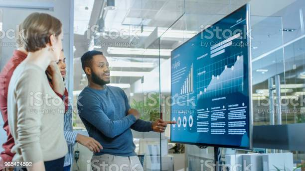 Diverse Team Of Young Professionals In Conference Room Have Discussion About Statistics And Graphs Shown On A Presentation Tv Stock Photo - Download Image Now