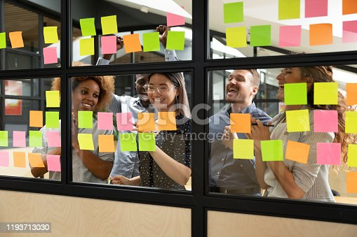 Overjoyed african american and caucasian teammates celebrating profitable startup project finish while smiling vietnamese team leader marking colorful stickers on kanban scrum glass window wall board.