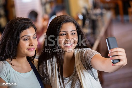istock Diverse teen girls taking selfie photo with phone in library 506764518