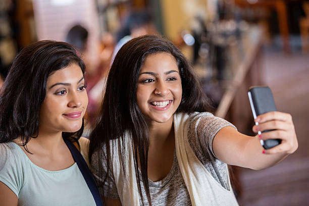 Diverse teen girls taking selfie photo with phone in library stock photo