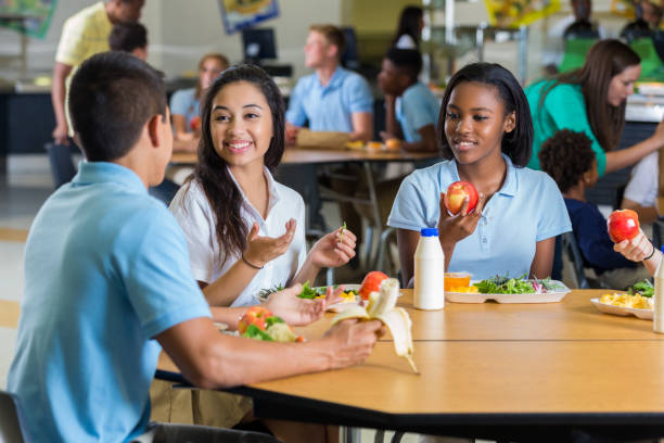 Diverse teenage friends eat lunch in school cafeteria stock photo
