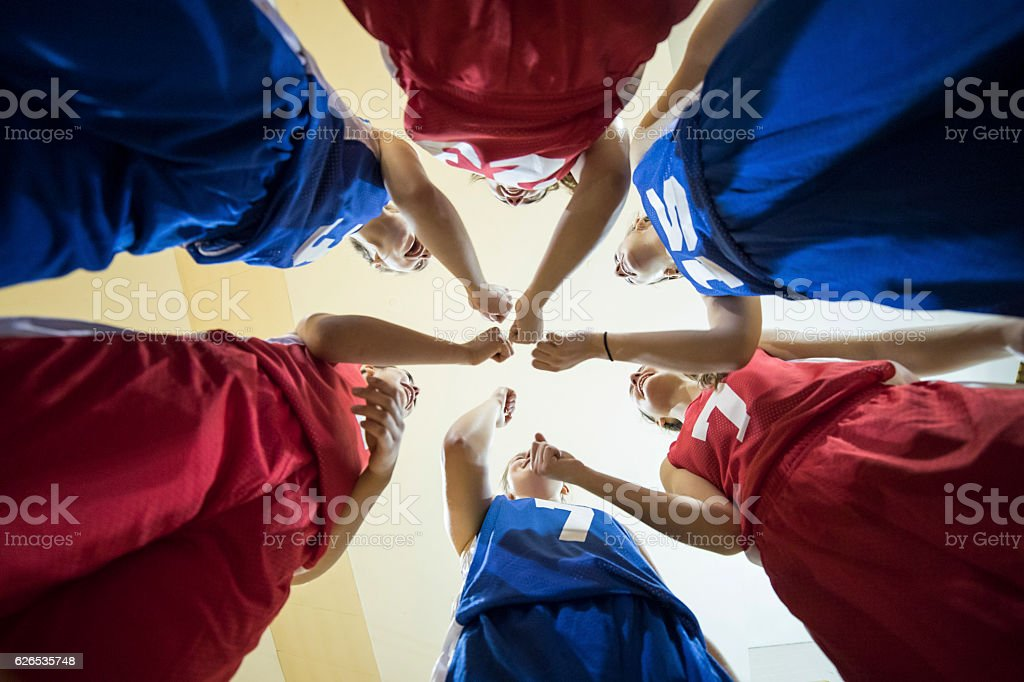 Diverse teenage girl athletes cheering after their team huddle stock photo