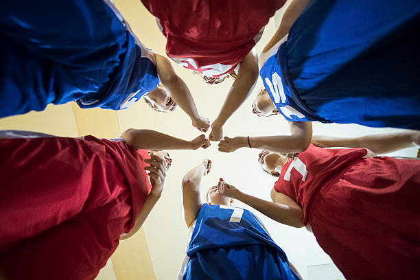 Diverse teenage girl athletes cheering after their team huddle - foto stock