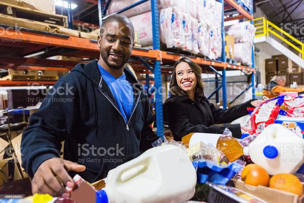 Diverse Volunteers cheerfully sorting food items stock photo