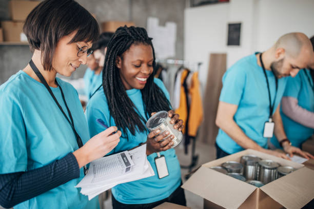 Diverse volunteers packing donation boxes in charity food bank stock photo