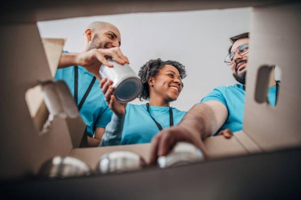 diversos voluntarios empacando cajas de donación con alimentos enlatados en banco de alimentos - giving tuesday fotografías e imágenes de stock