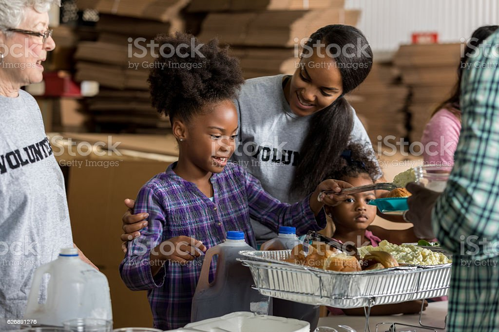 Diverse volunteers serve food in soup kitchen stock photo