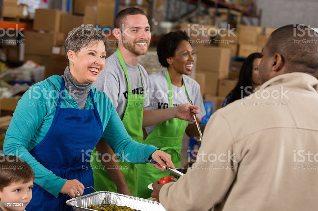 Diverse volunteers serving hot meal at community food pantry stock photo