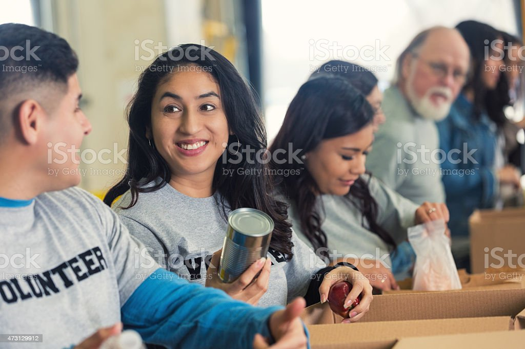 Diverse volunteers sorting food into cardboard boxes for charity stock photo