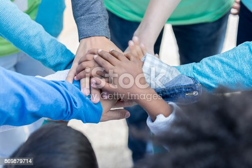 866758230 istock photo Diverse volunteers with hands together in unity 869879714