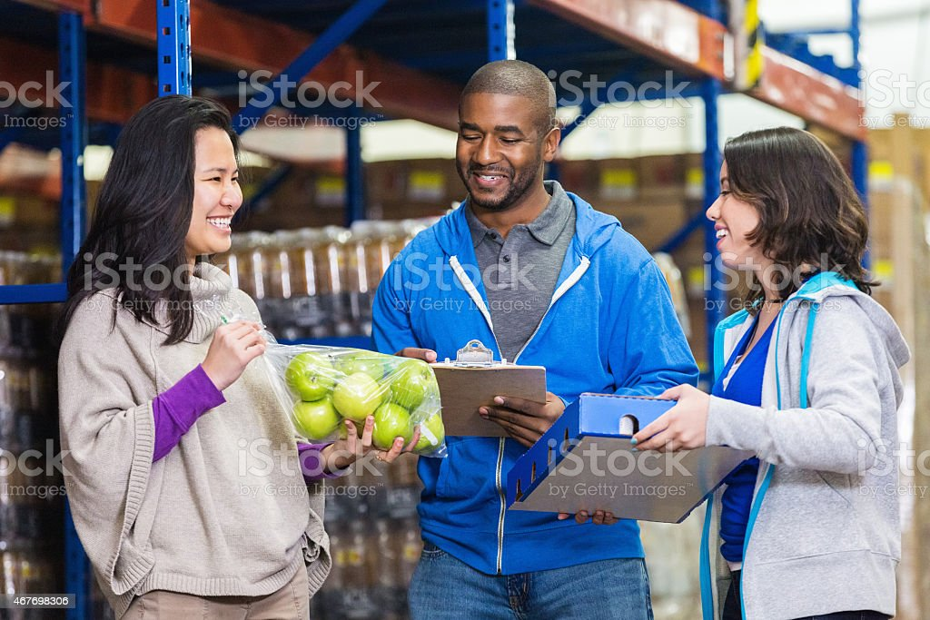 Diverse volunteers working in food bank distribution warehouse stock photo