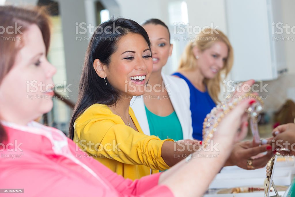 Diverse woman shopping during direct sales jewelry show stock photo