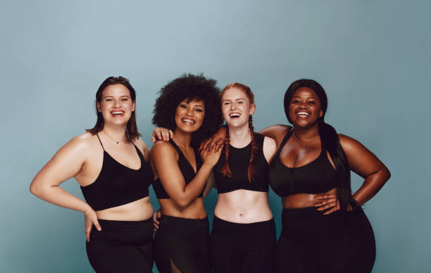 Diverse women embracing their natural bodies Portrait of group of women posing together in sportswear against a gray background. Multiracial females with different size standing together looking at camera and smiling. body positive stock pictures, royalty-free photos & images