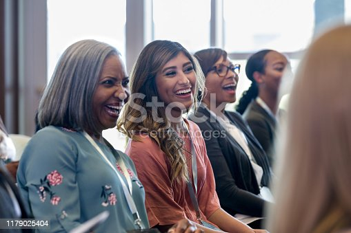 A diverse group of women enjoy a hearty laugh during a session during the expo.