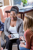 istock Diverse women hold hands during support group meeting 639865426