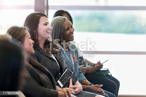 A group of diverse women sitting on the front row enjoy the comments made by the speaker at the conference.