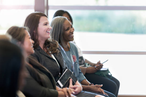 Diverse women in front row enjoy comments by unseen presenter stock photo