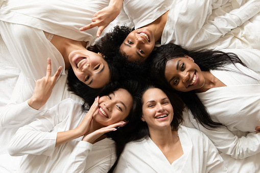 Top view five diverse women in white bathrobes lying in bed smile look at camera feels happy after body treatment, day spa procedures, resort beauty salon satisfied clients, bachelorette party concept