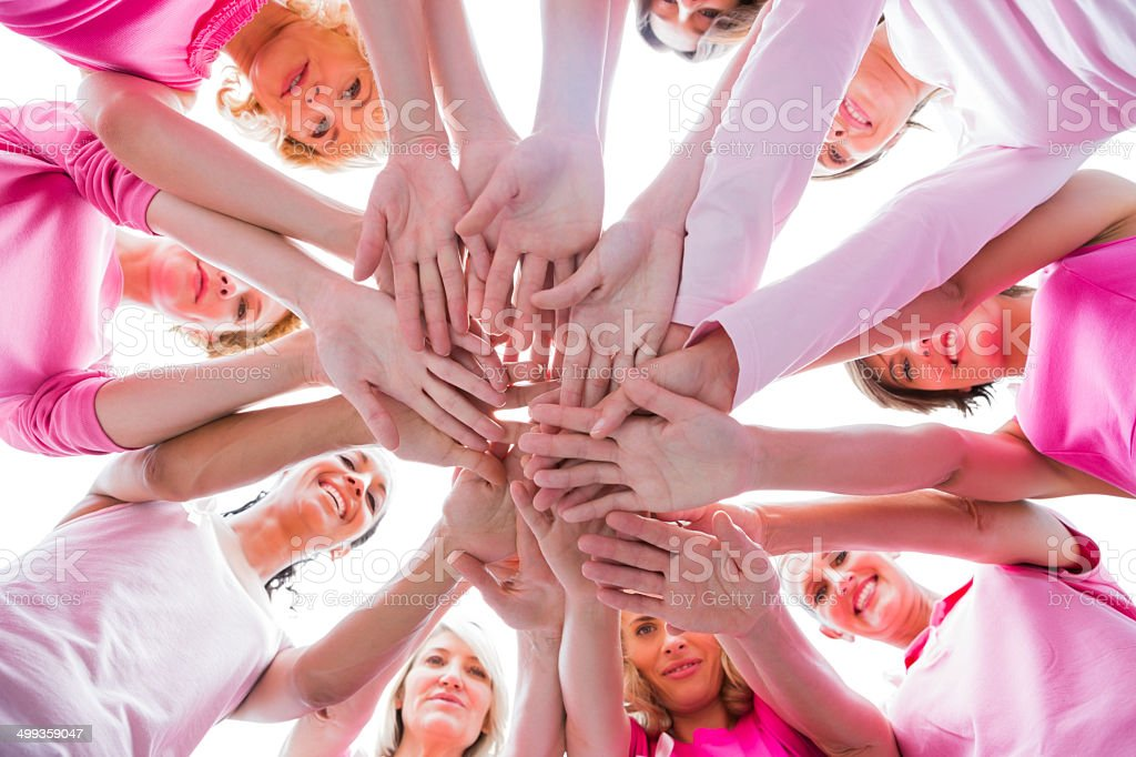 Diverse women smiling in circle wearing pink for breast cancer stock photo