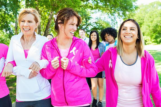 diverse frauen walking in brustkrebs marathon - laufveranstaltungen stock-fotos und bilder