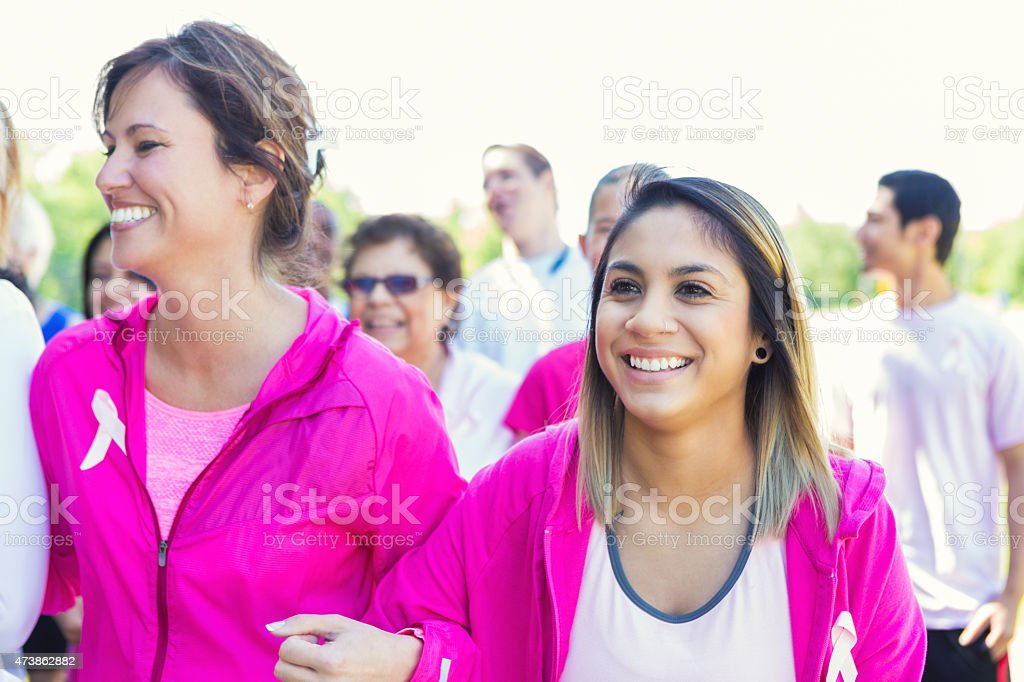 Diverse women walking together during breast cancer awareness race stock photo