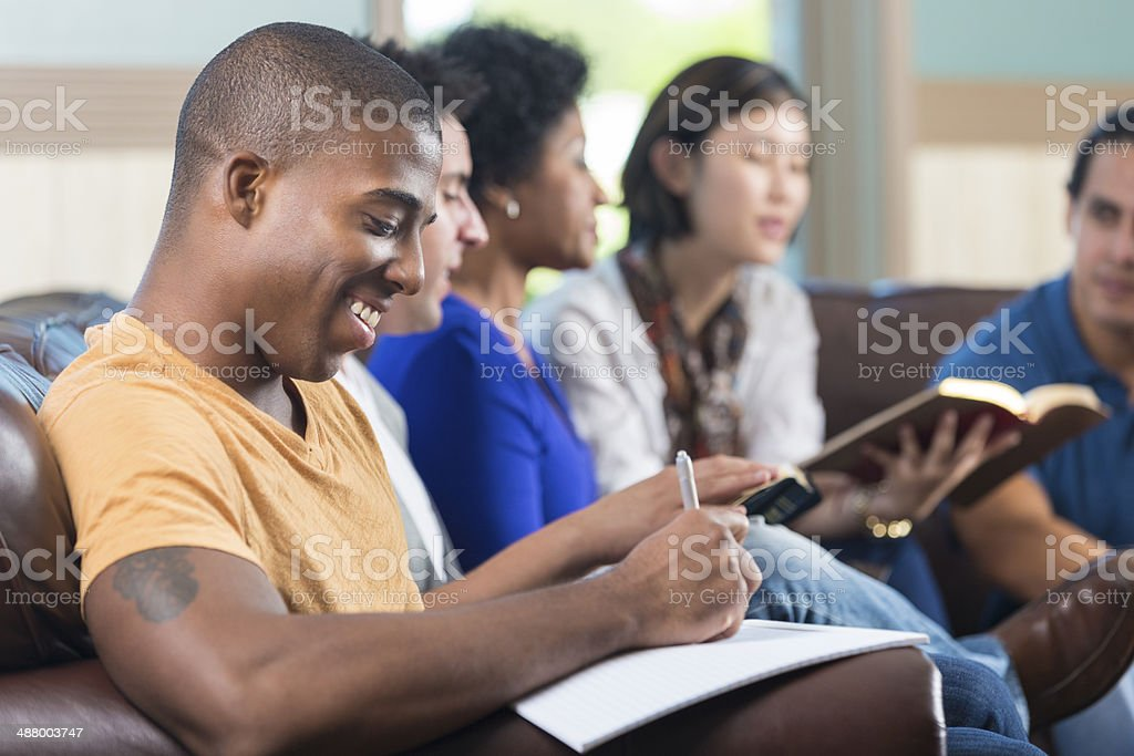 Diverse young adults having bible study at  home stock photo