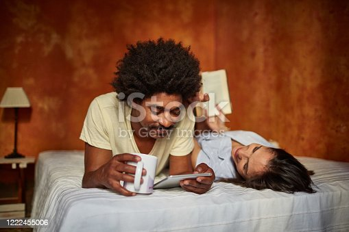 Compatible Caucasian and Afro-Caribbean couple in 20s and 30s lying next to each other on bed enjoying reading and coffee.