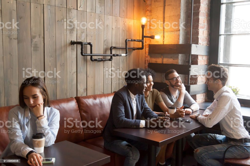 Diverse young friends ignoring sad girl sitting alone in cafe stock photo