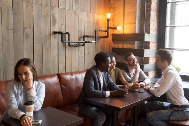 diverse young friends ignoring sad girl sitting alone in cafe - disbarment stock pictures, royalty-free photos & images