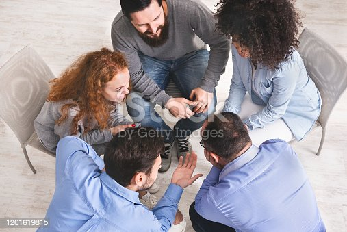 541975802 istock photo Diverse young people sitting in circle discussing working plan, top view 1201619815