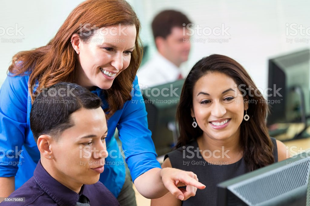 Diverse young professionals taking computer job training course stock photo