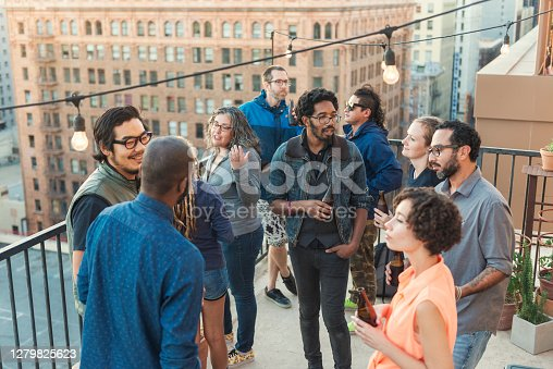 Horizontal color image of multi-ethnic group of friends having a roof party in downtown Los Angeles.
