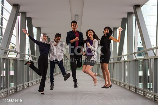 938516440 istock photo Diversity group of young multi cultural and multi racial people jumping and celebrating of business success 1128824419