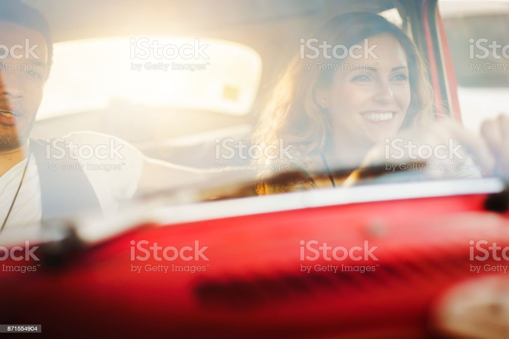 Diversity: multiethnic couple in a red vintage car - foto stock