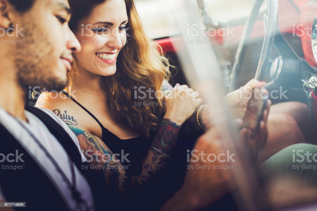 Diversity: multiethnic couple in a red vintage car stock photo