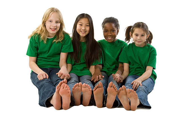 Diversity: Multi-Ethnic Group of Girls Go Green Sitting Holding Hands stock photo