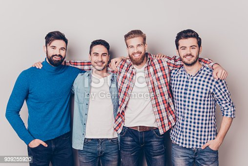 istock Diversity of men. Four cheerful young guys are standing and embracing, smiling, on pure background in casual outfit and jeans 939255920