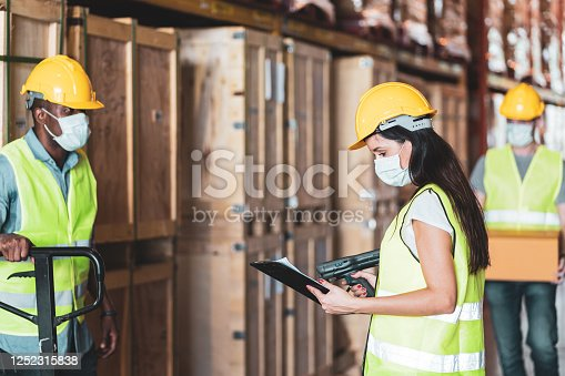 Group of diversity workers (Caucasian, Hispanic, Black) in protective face shield and mask and helmet check stock in warehouse. Concept of new normal work in factory, industry after Covid 19 pandemic
