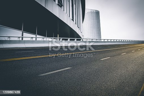 637668332 istock photo Divided highway passing through city buildings, blue nostalgia high contrast 1209867439